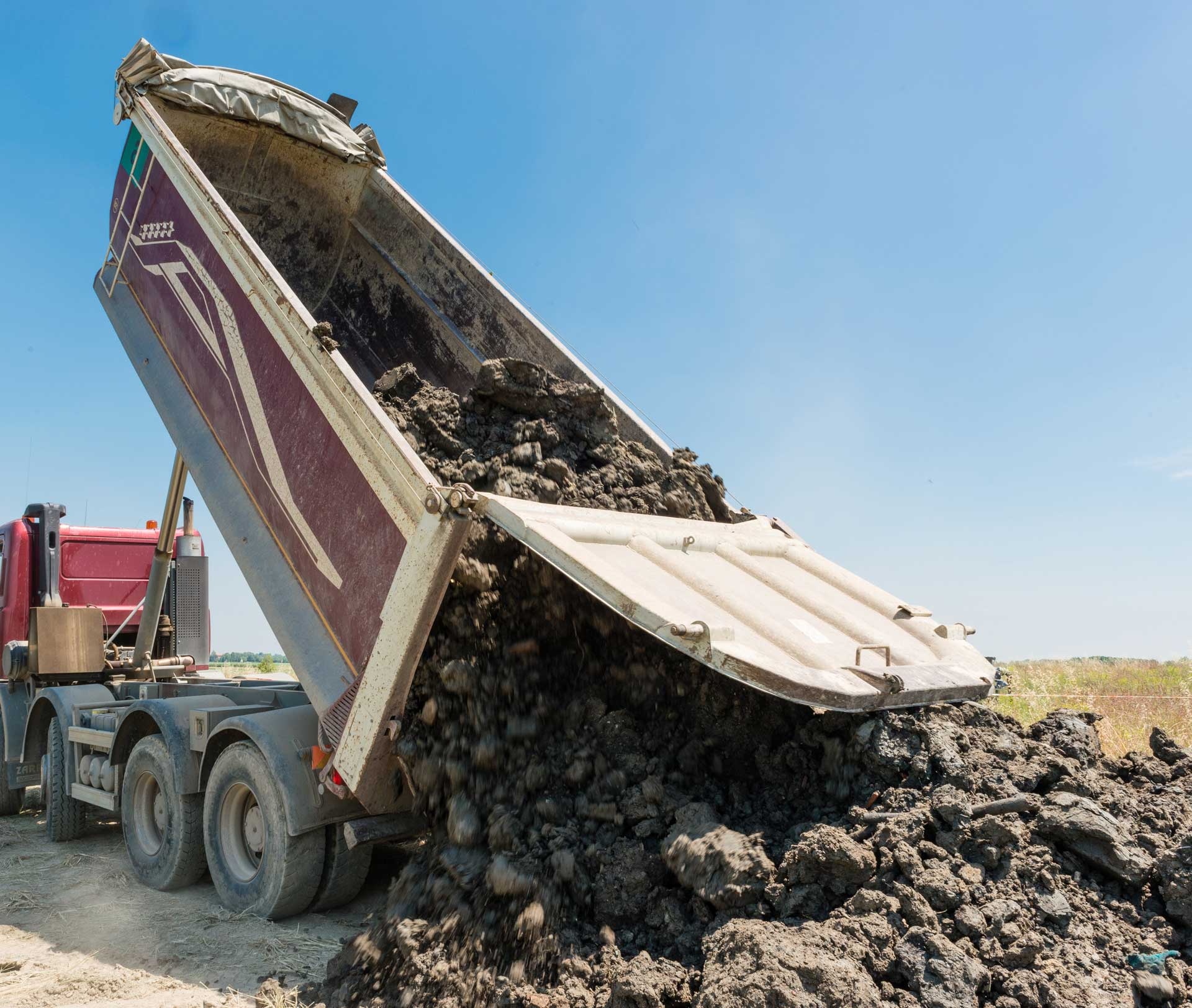 Image of dump truck off loading unscreened topsoil